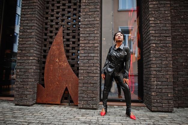 通りで黒い革のジャケットとズボンでポーズをとるファッショナブルな美しいアフリカ系アメリカ人の女性。
