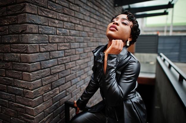 通りで黒い革のジャケットでポーズをとるファッショナブルな美しいアフリカ系アメリカ人女性。鼻のイヤリング。