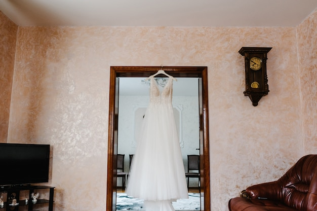 Модное красивое классическое кружевное шелковое платье невесты висит на вешалке в комнате. утренняя подготовка свадебной концепции. винтажное платье.