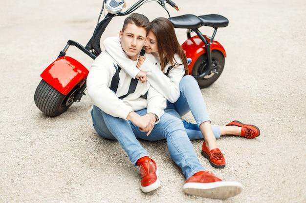 Модная красивая пара в джинсовой одежде в красных туфлях сидит и расслабляется возле электрического велосипеда