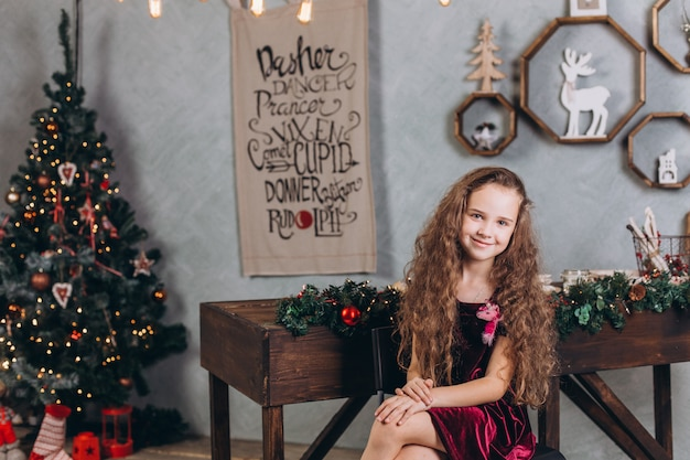 Fashionable beautiful girl in dress at home near new year eve and christmas decorations and colorful lights