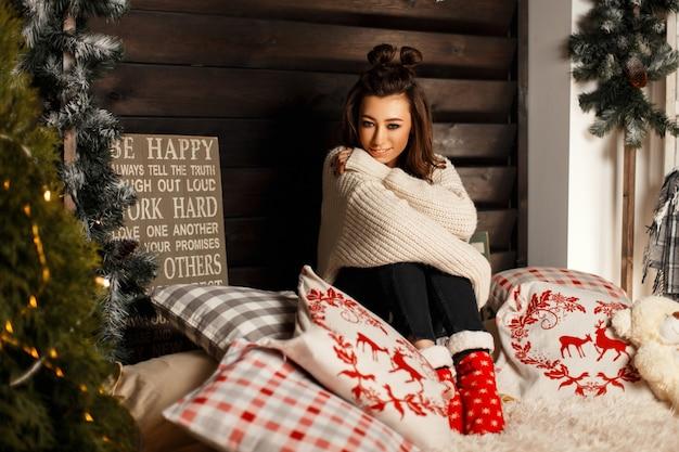Модная красивая девушка модель в винтажном вязаном свитере с красными теплыми носками на кровати