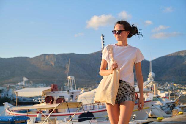 桟橋、海に沈む夕日、湾に係留されたヨット、山の風景の背景を歩くファッショナブルな美しい少女ティーンエイジャー。サングラスの女の子、エコバッグ付きショートパンツ