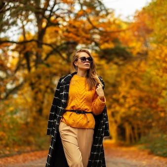 빈티지 옷에 선글라스를 끼고 세련된 검은 코트와 니트 스웨터를 입은 세련된 미녀가 공원을 산책합니다.