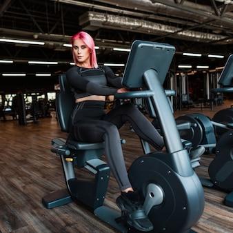 ピンクの髪とスニーカーで黒い服を着たほっそりした体を持つファッショナブルな美しい健康的な運動少女は、エアロバイクに座ってジムで運動します