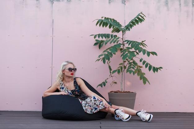 ピンクの壁の近くの椅子の袋に座っているスニーカーとスタイリッシュなサマードレスのファッショナブルな美しいモデルの女性