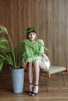 スタジオに座ってポーズをとるファッショナブルな美しいモデルの女性