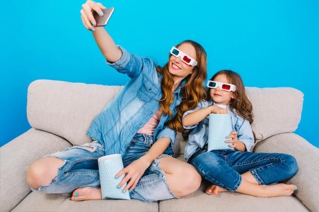 청바지 옷 파란색 배경에 고립 된 소파에 그녀의 어린 딸과 함께 selfie 초상화를 만드는 유행 아름 다운 어머니. 3d 안경 착용, 팝콘 먹기, 함께 영화보기