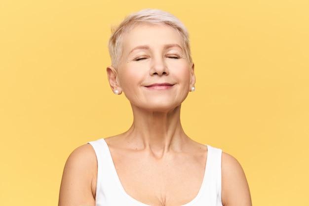 ピクシーの髪型をしたファッショナブルな美しい引退した白人女性は、目を閉じたままポーズをとり、喜びと楽しさで笑顔で、良い音楽を聴いたり、夢を見たりします。