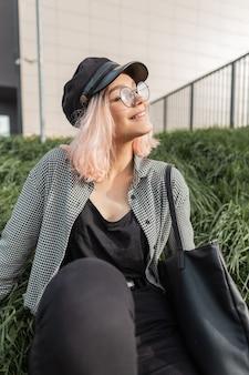 Модная красивая улыбающаяся девушка в винтажных очках в стильной клетчатой рубашке и черных джинсах с сумкой сидит на зеленой траве