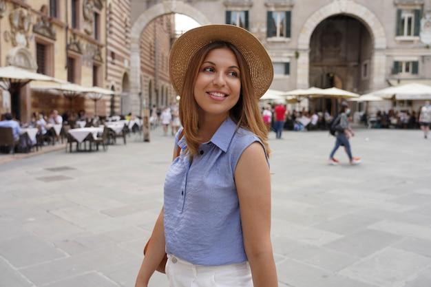 ヨーロッパでの贅沢なツアーのためにヴェローナの旧市街を散歩するファッショナブルな美しい女性