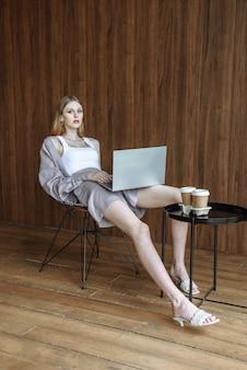 노트북이 의자에 앉아 있는 세련된 미녀