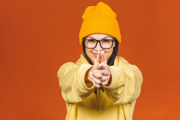スタイリッシュな服を着ているファッショナブルな美しい若い白人若い女子学生。オレンジの上に分離されました。
