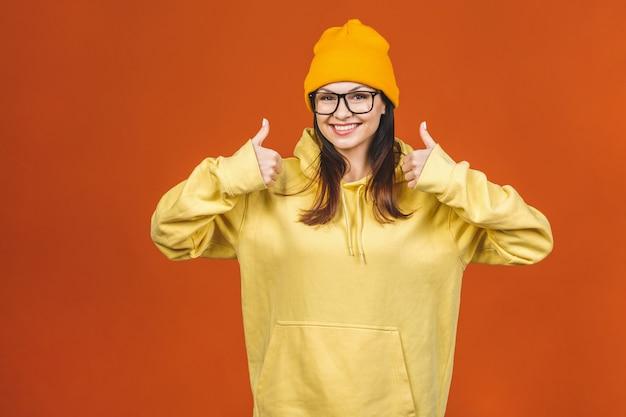 ファッショナブルな美しい若い白人若い女子学生がスタイリッシュな服を着て笑って、指を指しています。オレンジの上に分離されました。いいぞ。 Premium写真