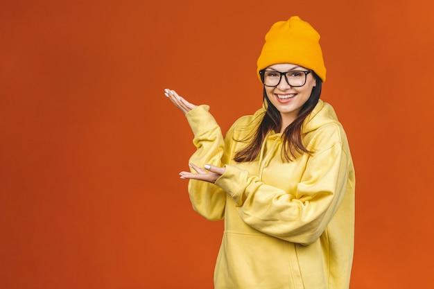 ファッショナブルな美しい若い白人若い女子学生がスタイリッシュな服を着て笑って、指を指しています。オレンジの上に分離されました。