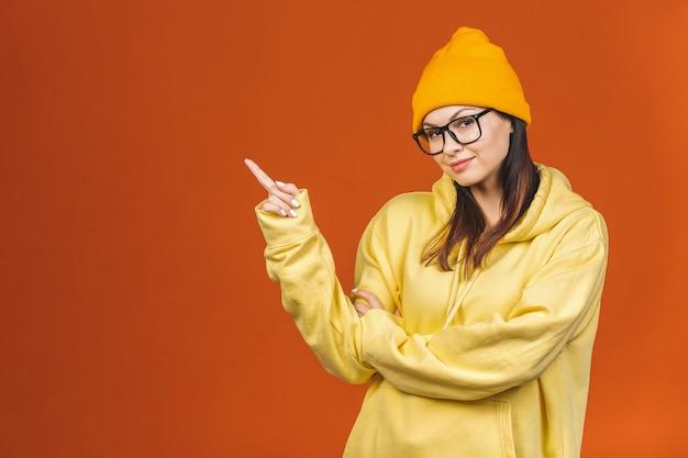 ファッショナブルな美しい若い白人若い女子学生がスタイリッシュな服を着て、指を指しています。オレンジの上に分離されました。