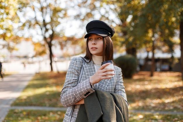 Модная красивая молодая девушка в шляпе и модном клетчатом костюме с кофе гуляет в парке в осенний солнечный день