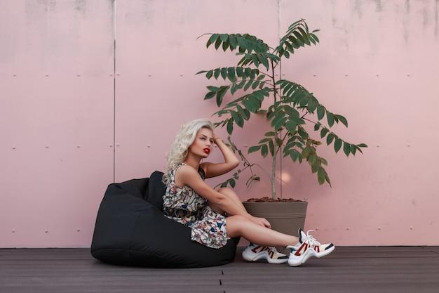 ピンクの壁の近くの鍋に緑の木とバッグの椅子に座っている靴とスタイリッシュなサマードレスのファッショナブルな美しい若いモデルの女性