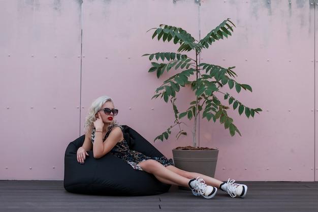 ピンクの壁の近くに座っているヴィンテージのドレスと靴のサングラスとファッショナブルな美しい若いモデルの女性