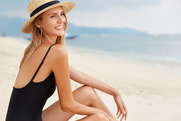 Fashionable beautiful young woman in black swimsuit sits on beach, admires azure ocean view and cloudless sky, recreates at sandy beach, sunbathes and feels relaxed. female tourist explores new places
