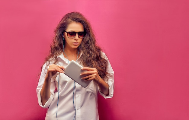 Fashionable beautiful young woman in a white shirt  in glasses with headphones, holding  a white tablet in hands on a pink colorful wall