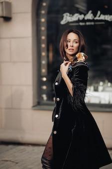 Молодая женщина модной красоты в модной одежде, идущей на открытом воздухе в центре города. красивая стильная брюнетка девушка в черной верхней одежде позирует в окружении экстерьера здания