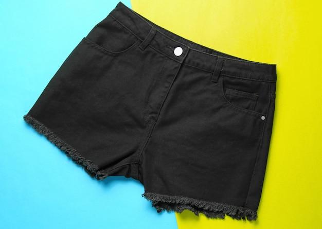 Fashionable black denim shorts on paper background. top view. minimalism fashion concept