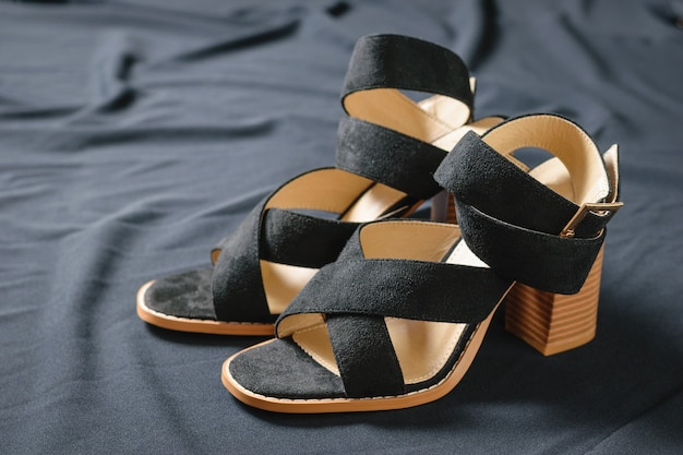 Fashionable black summer suede shoes on black fabric surface