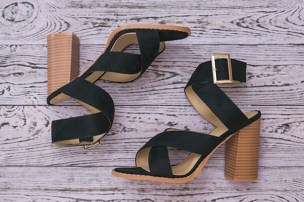 Fashionable black women's summer shoes on a wooden