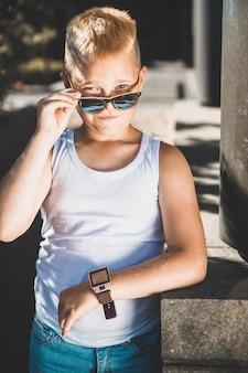 Модный белокурый мальчик в белой футболке в парке. вертикальная рамка