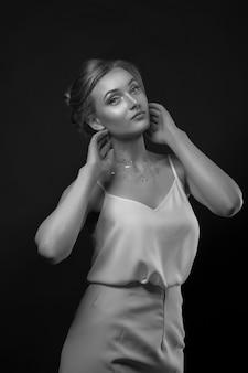 ファッショナブルな金髪の女性は、スタジオで影にポーズをとって白いシルクのドレスを着ています。黒と白のショット