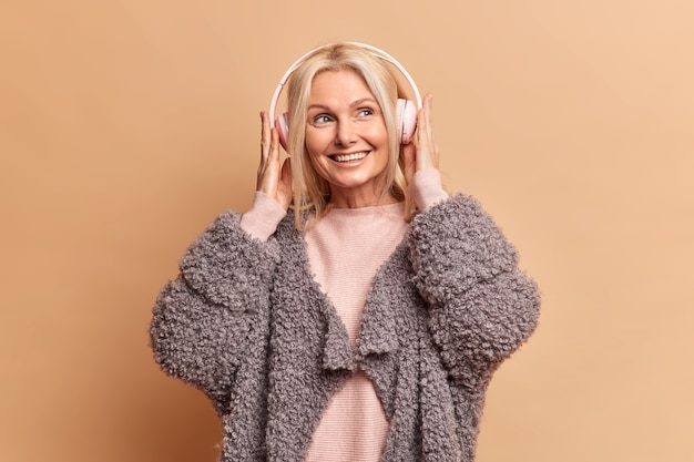 즐거운 미소를 지닌 세련된 금발의 유럽 여성은 스테레오 헤드폰을 착용하고 좋아하는 음악을 즐깁니다. 꿈꾸는 표정이 갈색 벽 위에 절연 모피 코트를 입습니다.