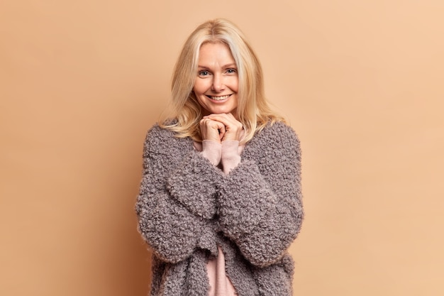 Fashionable blonde forty years old woman keeps hands under chin and smiles gently wears warm winter coat has minimal makeup poses against brown studio wall