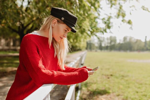 彼女の携帯電話を保持している流行の服を着たファッショナブルなブロンドの女の子。インスピレーションを持って立っている素敵なyounf女性。