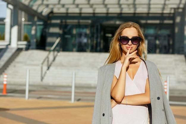 분홍색 드레스와 회색 재킷을 입은 세련된 안경을 쓴 세련된 금발 모델. 텍스트를 위한 공간