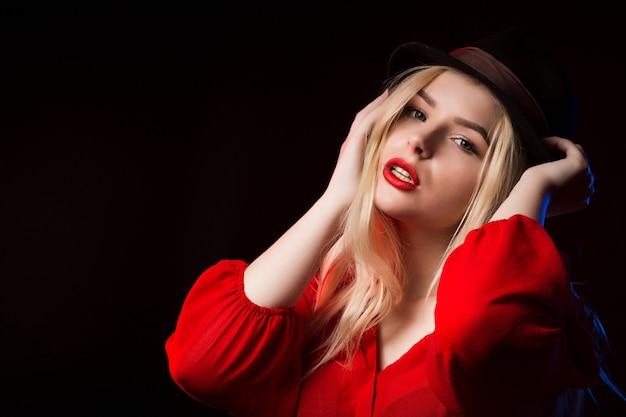彼女の顔に影を付けてスタジオでポーズをとって赤いブラウスと茶色の帽子のファッショナブルなブロンドの女性