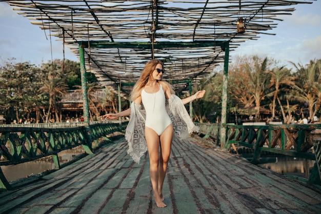 이국적인 장소에 흰색 수영복에 유행 금발 여자