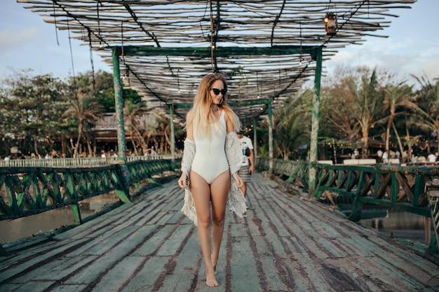 Модная блондинка в белых купальниках в экзотическом месте