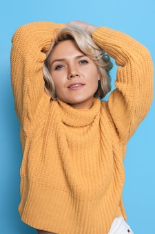 Fashionable blonde woman in a knitted sweater is posing at camera on a blue wall