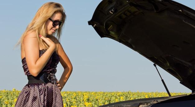 田舎のひまわり畑と一緒に故障した後、彼女の車のエンジンを見ているファッショナブルなブロンドの女性