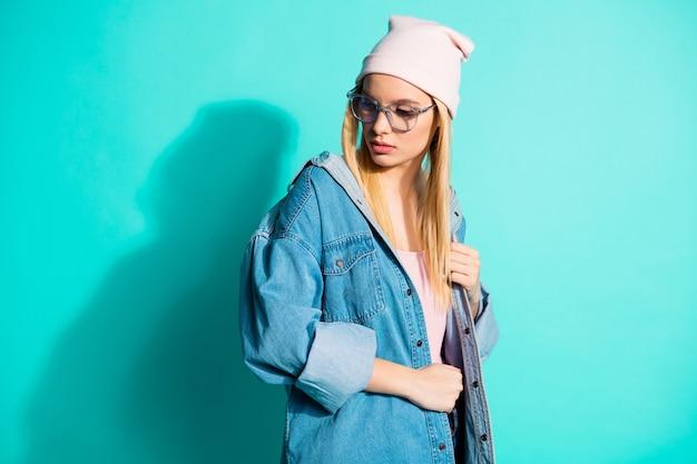 Модная блондинка позирует у синей стены