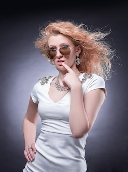 Fashionable blonde woman in sunglasses . isolated on a dark