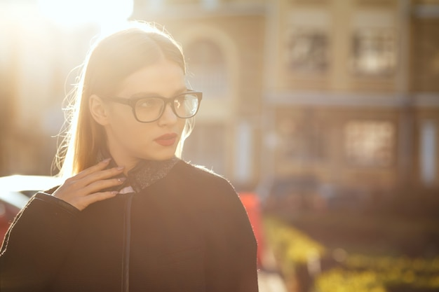 Fashionable blonde woman wears glasses and walking down sunny street. space for text