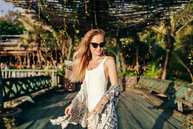 Fashionable blonde woman in white swimwear in exotic place