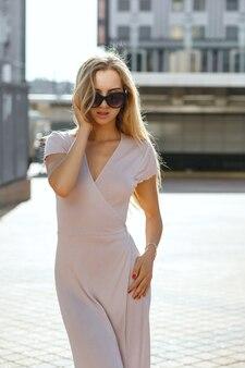 해질녘 거리를 걷고 있는 분홍색 드레스를 입은 긴 머리를 가진 세련된 금발 여성
