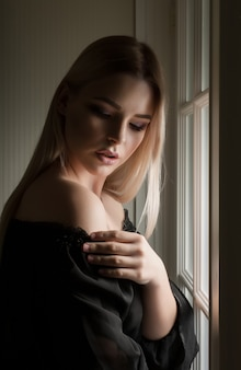 Fashionable blonde woman with naked shoulders posing in the dark room