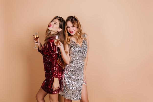 Donna bionda alla moda con sorriso sornione in posa con bicchiere di vino vicino al migliore amico