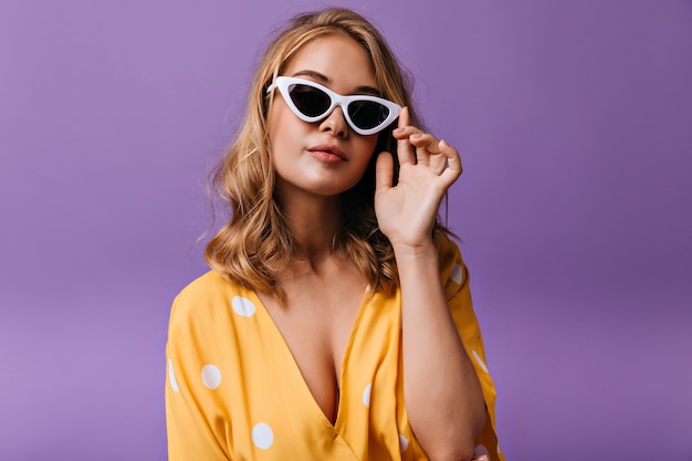 Fashionable blonde woman in yellow clothes posing in elegant sunglasses. serious caucasian female model standing on purple.