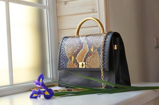 Модная женская сумка синего цвета с имитацией змеиной кожи. на нем маленькая ручка и длинная золотая цепочка. он стоит на фоне окон.