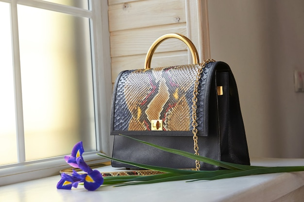 Fashionable blue colored woman s bag with snake skin imitation. it has a little handle and long golden chain on it. it stands on windows background.